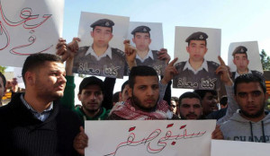 Students hold a sign reading in Arabic, 'You will stay a Falcon' and pictures of Maaz Al Kassasbeh in Amman