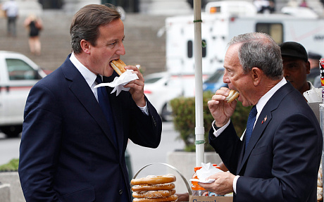 British Prime Minister David Cameron and then NYC mayor Michael Bloomberg eat a companionable hot dog outside Penn Station in New York