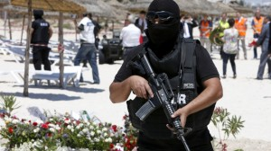 A hooded Tunisian police officer stands guard ahead of the visit to Sousse of top  British, French, German and Belgian officials to the scene of the June 26 tourist massacre