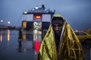 A man wrapped in a thermal blanket waits to get on board a ferry bound to Piraeus at the port of Mytilene, on the Greek island of Lesbos