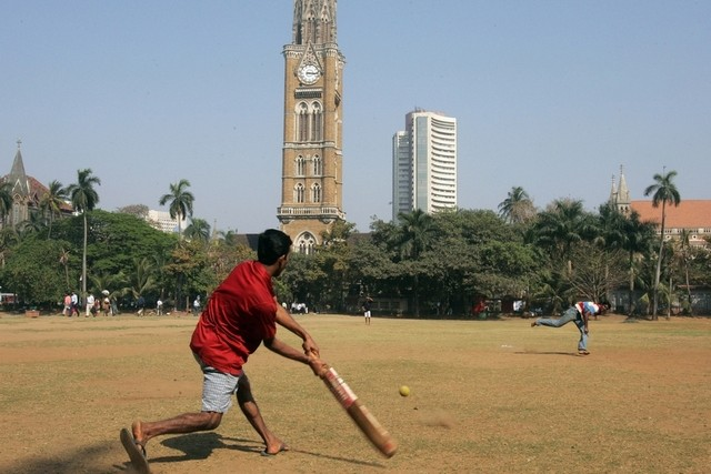 Residents of Mumbai play cricket as the Bombay Stock Exchange building is seen in the background (AP Photo/Rajesh Nirgude)
