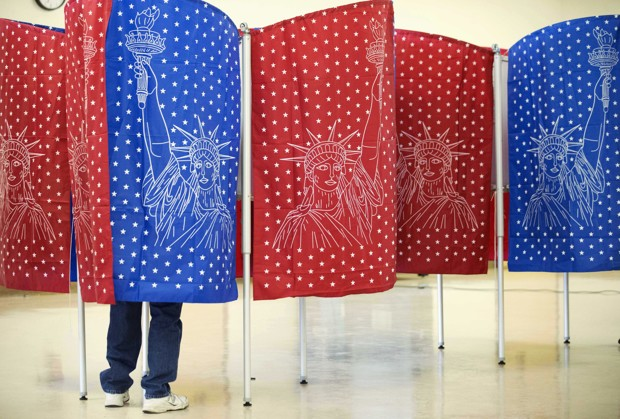 A voter marks a ballot for the New Hampshire primary inside a voting booth at a polling place Tuesday, Feb. 9, 2016, in Manchester, N.H. (AP Photo/David Goldman)