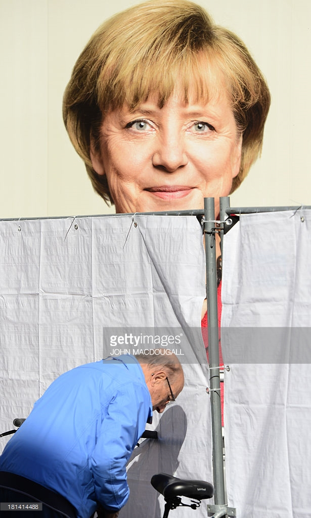 A man locks his bike next to an election campaign poster featuring German chancellor Angela Merkel