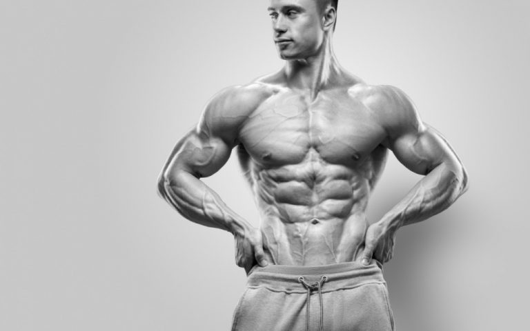 Handsome power athletic young man with great physique. Strong bodybuilder with six pack, perfect abs, shoulders, biceps, triceps and chest. Studio shot on white background