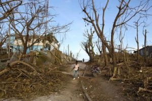 A man walks past the debris left by Hurricane Matthew in Dame-Marie, Haiti on Monday, Oct. 10, 2016. Nearly a week after the storm smashed into southwestern Haiti, some communities along the southern coast have yet to receive any assistance, leaving residents who have lost their homes and virtually all of their belongings struggling to find shelter and potable water. (AP Photo/Dieu Nalio Chery)