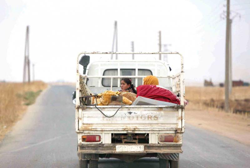 On the verge of disaster. Civilians ride in the back of a truck as they flee villages that were taken over by Turkey-backed fighters in the countryside of Tal Abyad, October 24. (AFP)