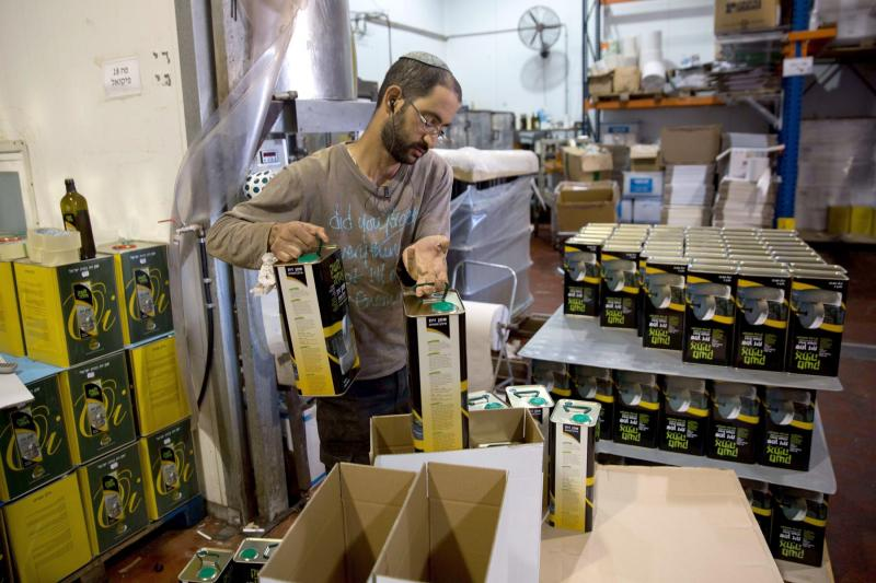 The right to know. An Israeli settler prepares olive oil containers at the Achia Olive press factory in the Jewish settlement of Shilo in the occupied West Bank